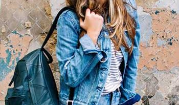 Girl wearing a denim jacket with t-shirt and jeans and carrying a backpack