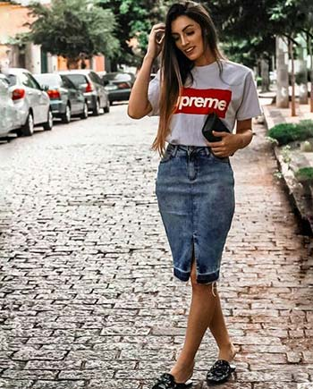 Girl wearing a knee-length denim skirt and t-shirt while walking down a street