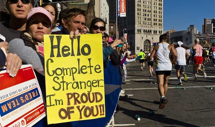 "Crowed of people holding up a sign that reads: ""Hello complete stranger, I'm proud of you!"" at the New York Marathon"