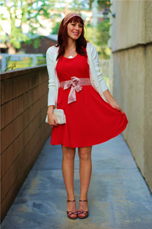Young woman wearing red skater dress with white cardigan/shrug