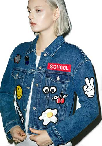 Young woman wearing denim jacket with patches