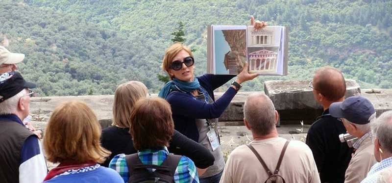 Female tour manager speaking to a group of tourists