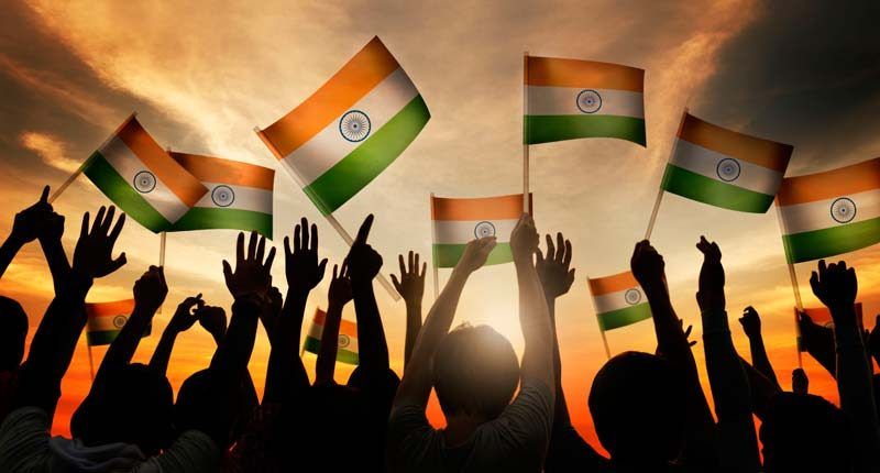 Silhouettes of youngsters waving Indian flags