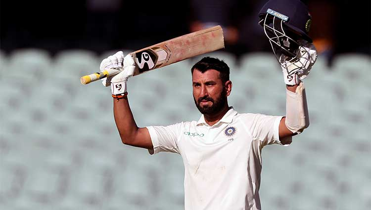 Cheteshwar Pujara lifting his arms up in celebration