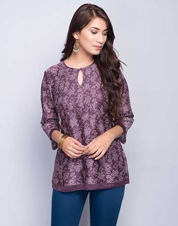 Young woman wearing a purple printed kurti with blue jeans