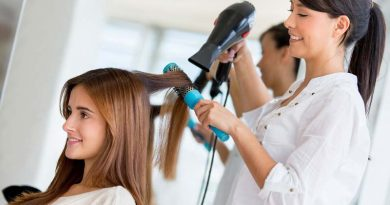 Female hair stylist blow drying female client's hair