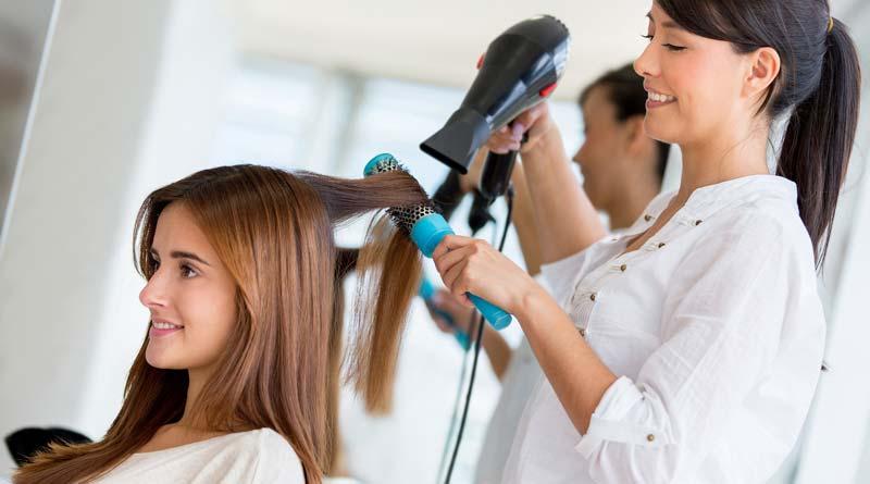 Female hair stylist blow drying female client's hair