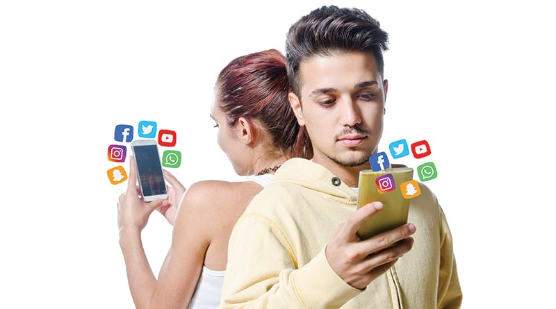Young guy and girl backing each other and busy on social media