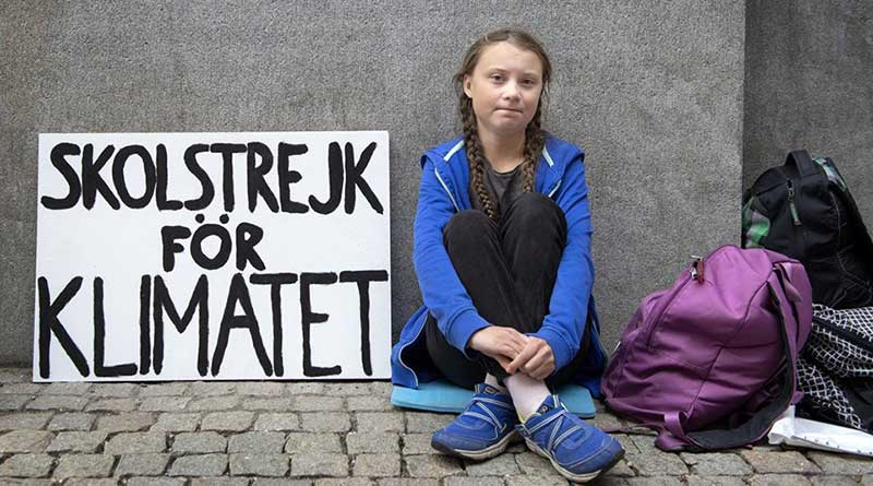 Greta Thunberg sits outside the Swedish Parliament with a banner reading 'School strike for climate'