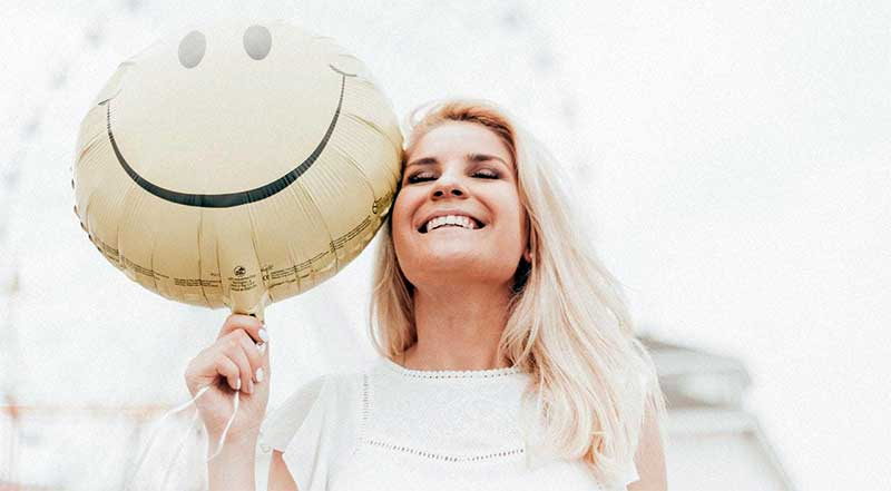 Woman carrying a smiley balloon
