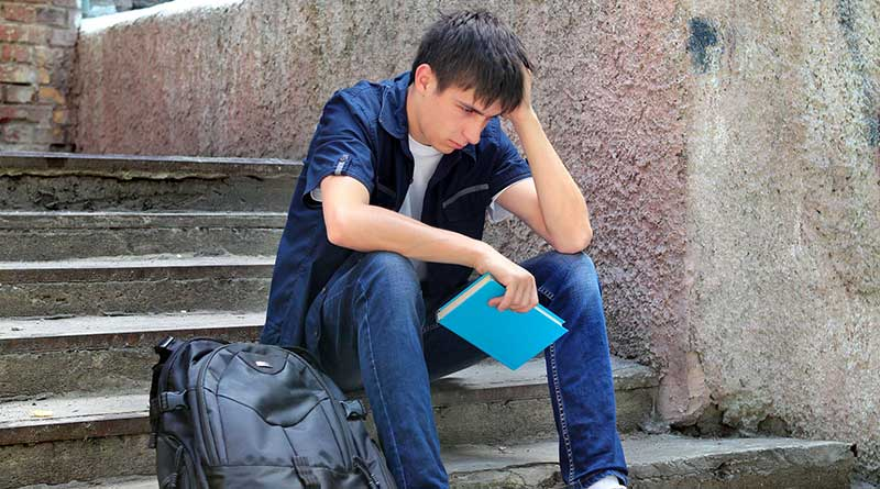 Sad student sitting on the steps of a house with his backpack
