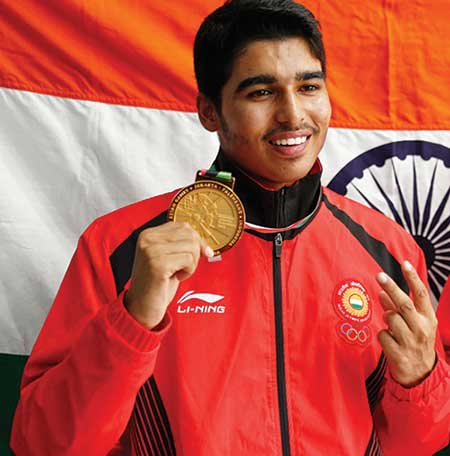 Saurabh Chaudhary holding up his gold medal in front of the Indian tricolour