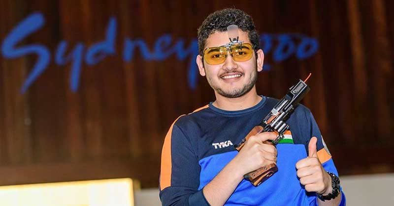 Anish Bhanwala holding his pistol and showing a thumbs up sign