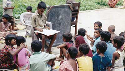 Babar Ali, aged 11 or 12, teaching children from his village in Murshidabad after returning from school.