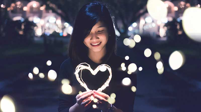 Young girl holding up a heart shape with lights