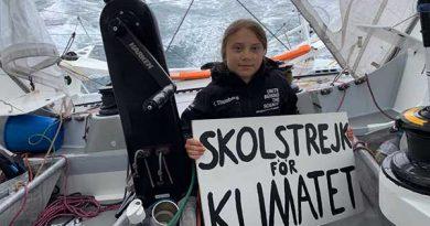Greta Thunberg holds up a sign on board the Malizia II