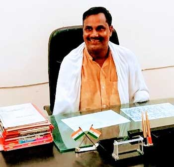 Shreenarayan sitting at his desk