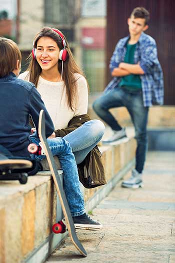 Upset boy looking at happy teen girl and boy sitting together