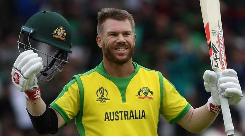 David Warner raising his bat in the air in celebration