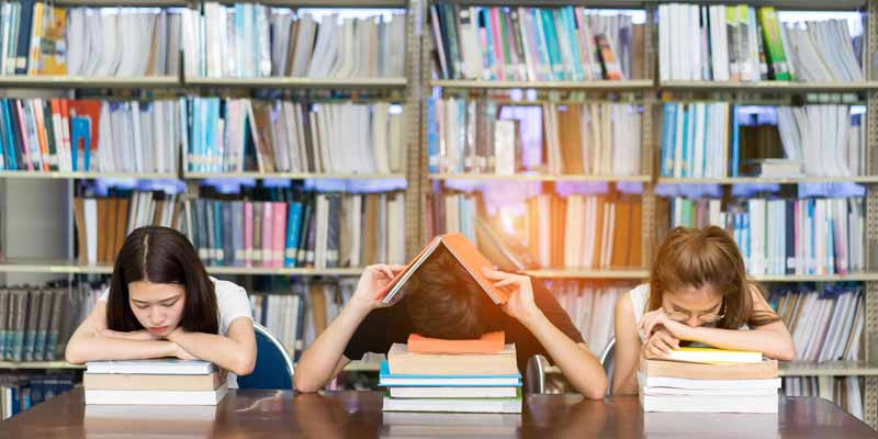 Students suffering from exam stress in library