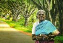 Saalumarada Thimmakka standing in front of a row of trees