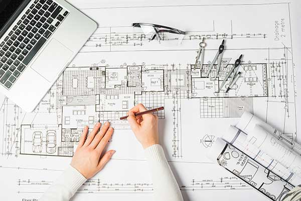 Architect using drawing tools on planning board
