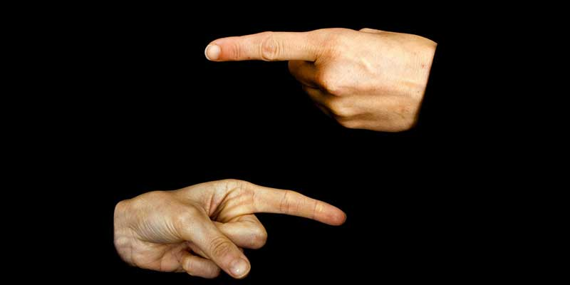 Fingers of two hands pointing at each other