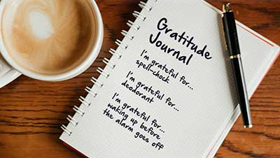 Gratitude journal next to a cup of coffee