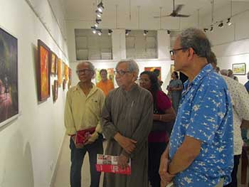 Eminent artist Ganesh Haloi (second from right) evaluating Manoj's painting at an exhibition.