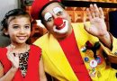 Pravin Tulpule dressed as a clown cheering up a small girl