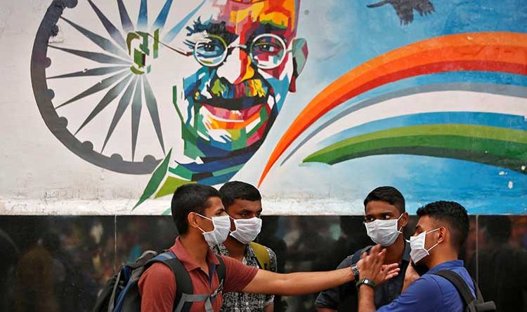 Young men with face masks standing in front of a billboard with image of Gandhi and Indian flag