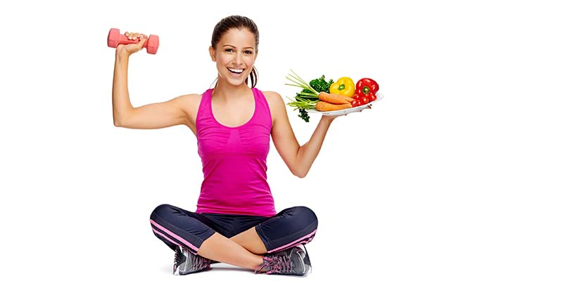 Young woman in exercise gear holding dumbells and a plate of healthy food