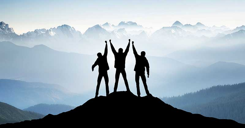 Mountain climbers standing at the top of a mountain with arms raised in victory