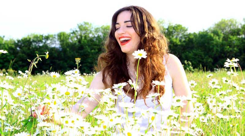 Happy, optimistic young woman in a field of daisies