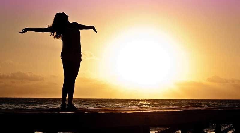 Young woman with her arms outstretched in acceptance at sunset