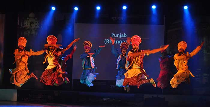 Men performing the Bhangra Dance on stage