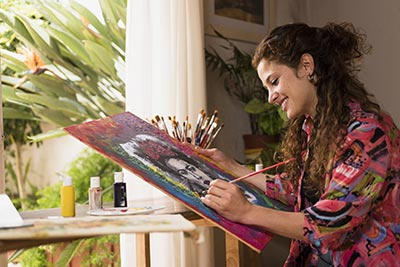 Young woman smiling and painting