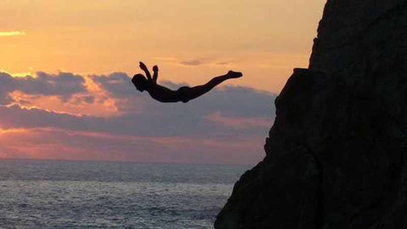 Silhouette of a man diving off a cliff
