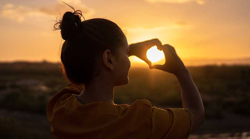 Girl making a heart shape with hands at sunset