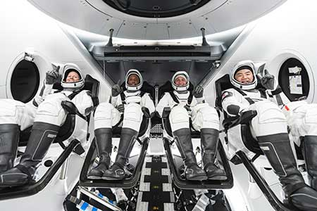 NASA's SpaceX Crew-1 crew members are seen seated in the company's Crew Dragon spacecraft during crew equipment interface training.