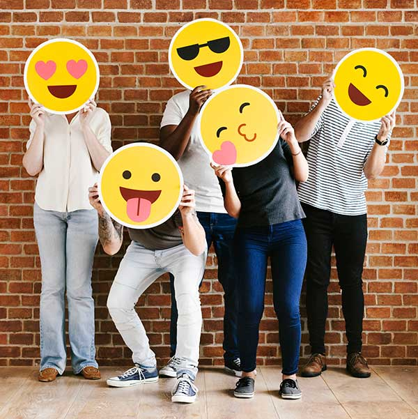 Teenagers holding up various emoticons