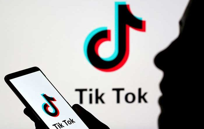 Silhouette of a person using TikTok app on smartphone