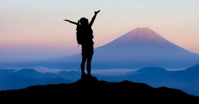 Young girl raising her hands up while standing on a mountain top