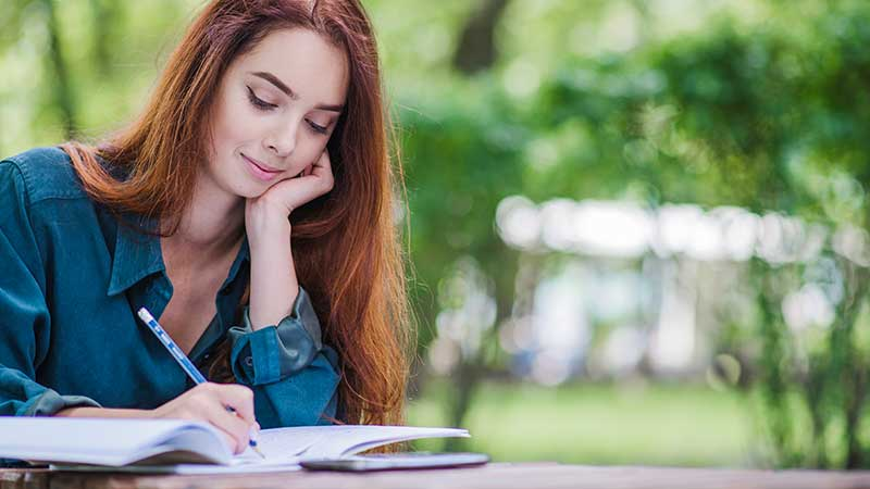 Young woman journalling in her diary