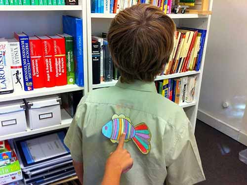 A paper fish being hung on the back of a boy as an April Fools' Day joke