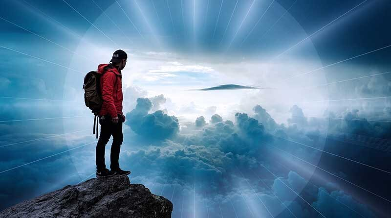 Man on a mountain-top looking at light in distance