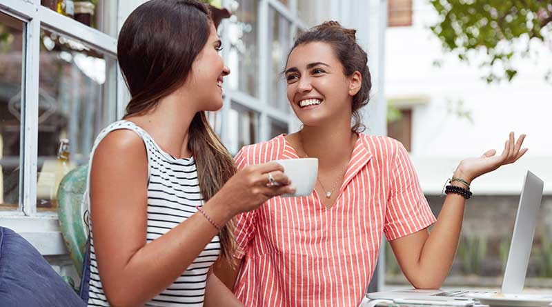 Two happy young women having a pleasant conversation