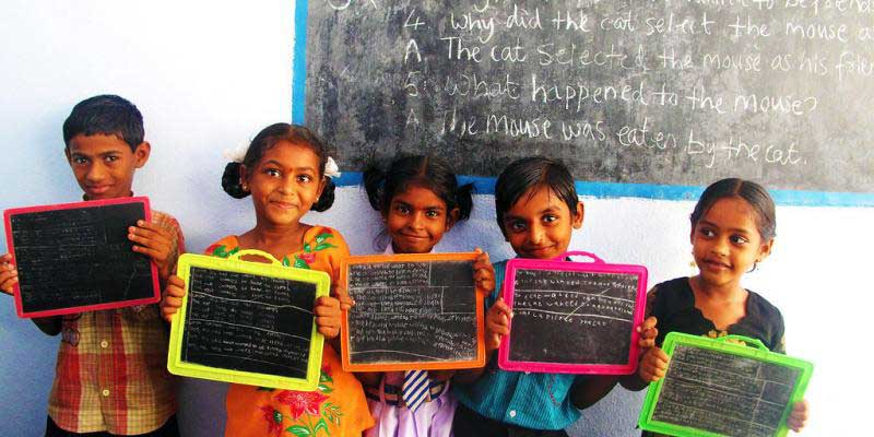 Children standing in front of blackboard with their slates