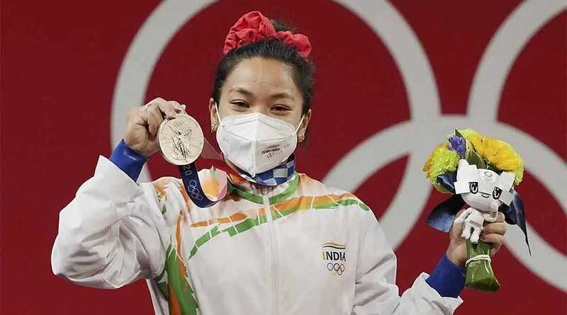 Mirabai Chanu holding up her Olympic silver medal for weightlifting