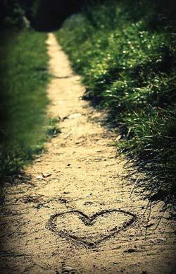 Heart traced on a sandy path